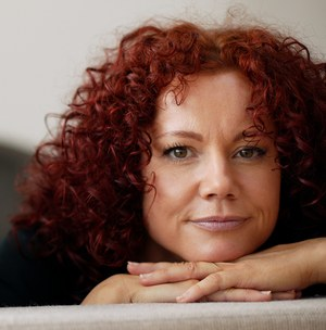 red haired woman with hands folded below her chin while looking into camera